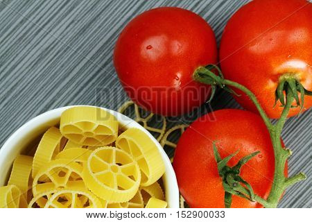 Overhead view of a bowl of Rotelle pasta and red tomatoes on grey background selective focus.