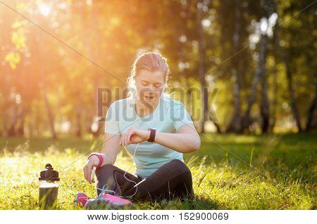 Woman Runner Sitting On The Grass Using A Smart Watch.