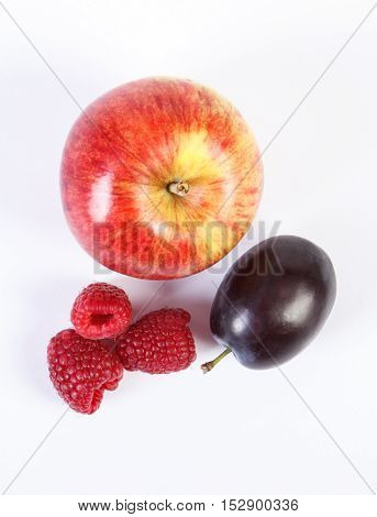 Fresh ripe apple raspberries and plum on white background healthy nutrition