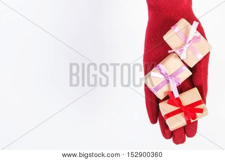 Hand Of Woman In Gloves With Gifts For Christmas Or Other Celebration, Copy Space For Text