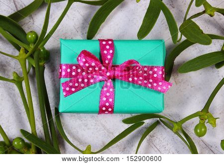 Wrapped Green Gift For Christmas And Mistletoe On Old Wooden Background