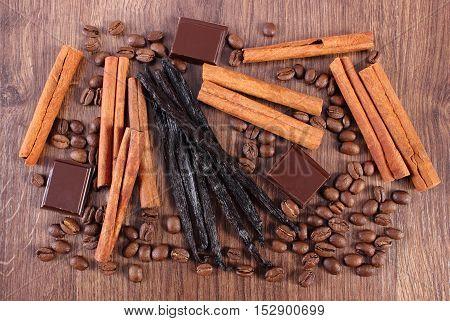 Vanilla, Cinnamon Sticks, Chocolate And Coffee Grains On Wooden Surface