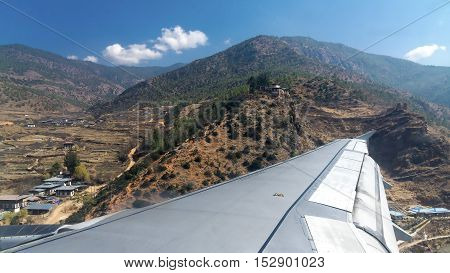 Wing of an airplane flying above the land and mountain before landing.