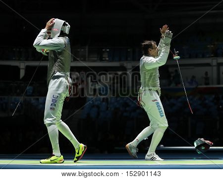 RIO DE JANEIRO, BRAZIL - AUGUST 12, 2016: Fencers Alexander Massialas of USA (L) and Alexey Cheremisinov of Russia compete in the Men's team foil of the Rio 2016 Olympic Games at the Carioca Arena 3