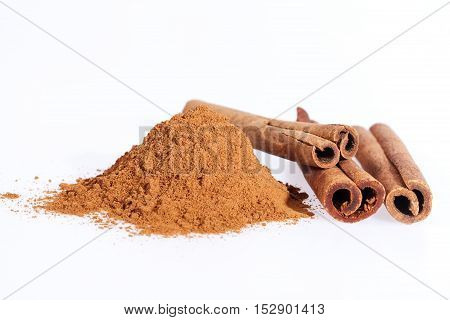 Cinnamon sticks and powder isolated on white background close up.