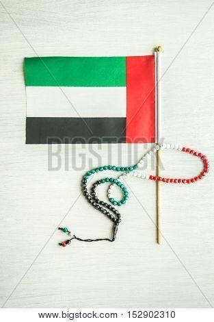 Small flag of UAE and a symbolic Islamic rosary. UAE National day celebration objects.