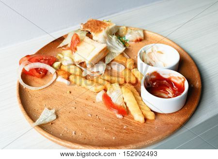 Junk food is wasted or spoiled food and other refuse in wood dish from a kitchen.