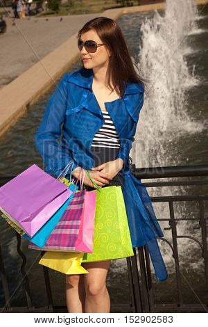 Cheerful young woman is resting after good shopping near fountain
