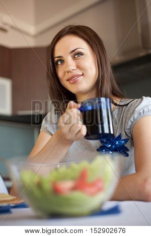 Woman is drinking her morning tea. With salad on the foreground out of focus.
