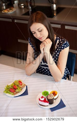 Young woman at her kitchen and choosing between diet sandwiches and fancy cakes