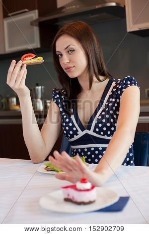 Young woman is choosing healthy food instead of cake