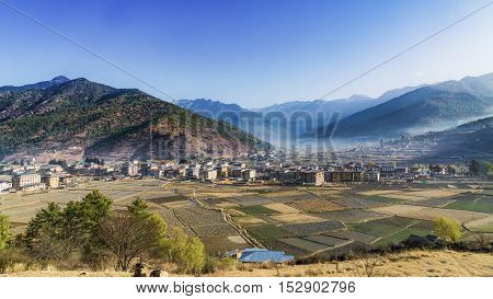 The village old town house architecture with the field grassland for faming which is a panorama view of valley mountain on the background of white cloud and blue sky Paro Bhutan. (Aeria top view)