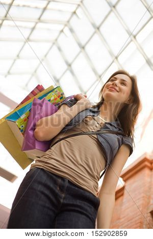 Young woman at shopping mall with shopping bagslow angle view