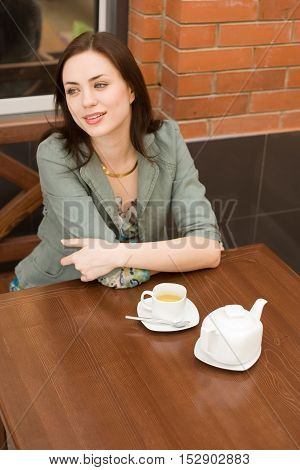 Young woman is sitting at the mallin the small restaurant with cap of tea