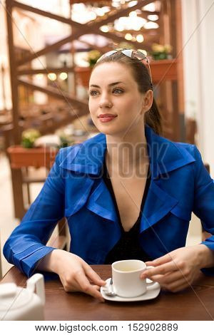 Young woman is sitting at the table and holding cap of tea in her hands