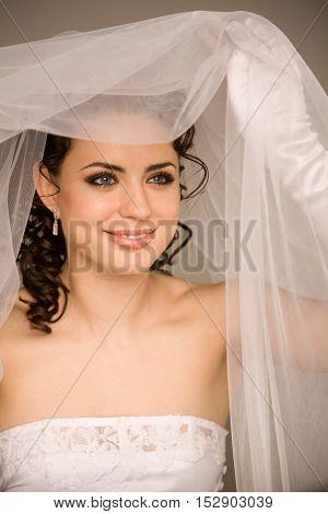 Happy bride holding the veil studio shoot