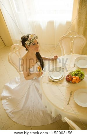Bride is sitting at the table and holding glass of wine