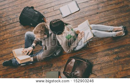 Girl and boy with a books sitting and studying on a floor. Vintage filter.