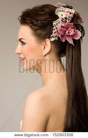 Portrait of the bride with gorgeous hairstyle with orchid