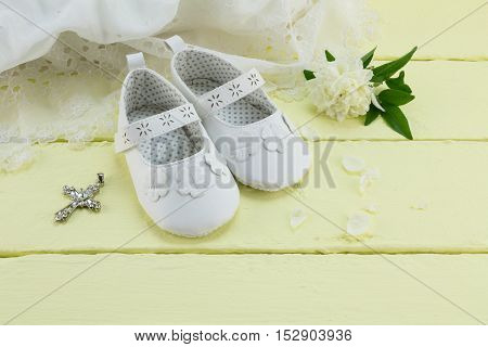 Pair of white baby booties on yellow background with cream rose flower and baptism dress