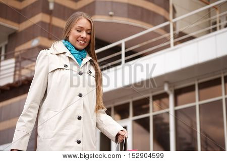 happy young woman holding shopping bags and smiling