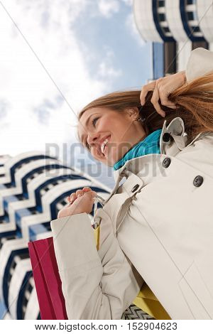 Woman is standing near modern building with shopping bags.Low Angle View