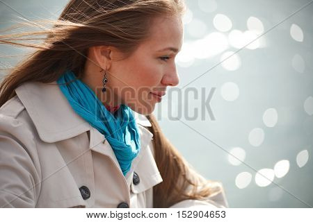 Young beautiful woman standing near water line