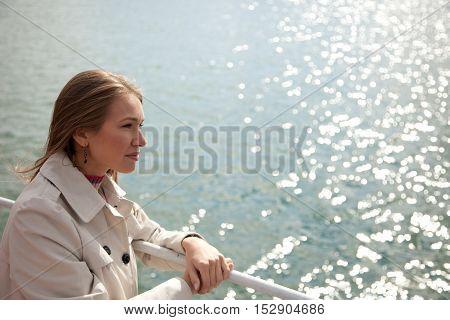 Young beautiful woman standing near water line .Copyspace