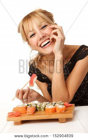 Young smiling woman with chopsticks in her mouth and sushi