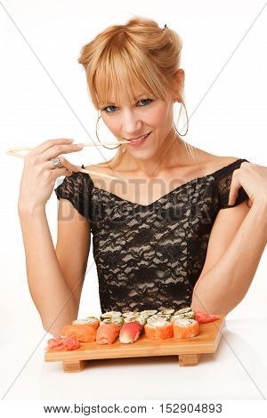 Young woman with chopsticks in her mouth and sushi
