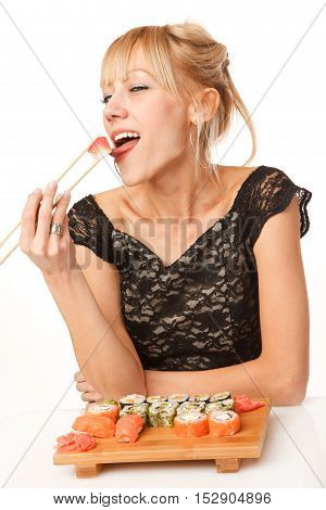 Young woman is trying sushi with her tongue