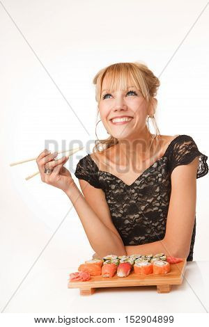 Young cheerful woman with chopsticks and sushi