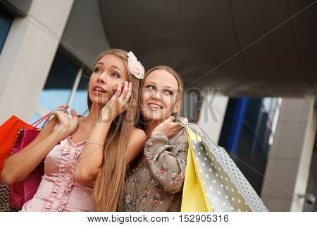 Two girls with shopping bags standing on the street one of the girls is talking on the phone