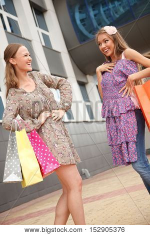 Two girls with shoppping bags standing on the streetone of them showing her new dress