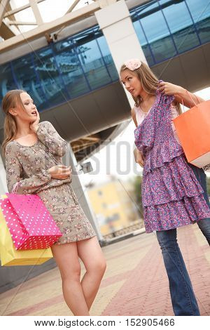 Two girls with shoppping bags standing on the street one of them showing her new dress