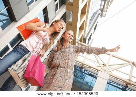 Two young women with shopping bags outdoors.One of girls shows to another direction.Low angle view