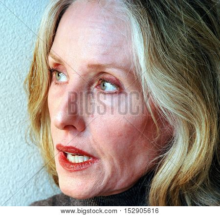 Mature female blond beauty expressions outside alone.