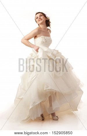 Young cheerful bride holds her dress studio shoot