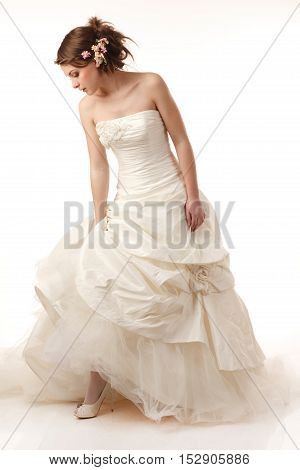 Gourgeus classical standing bride is looking down.WModern hairstyle with real flowers