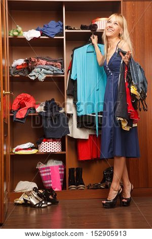 Beautiful young woman stands near her wardrobe and holding heap of clothes
