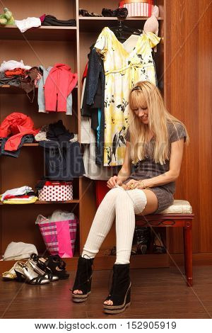 Sensual young woman is putting her leggings on near her wadrobe