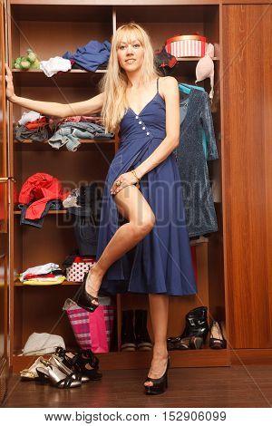 Woman in blue dress is standing near her wardrobe