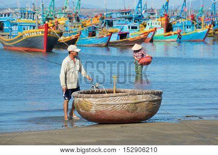 MUI NE, VIETNAM - DECEMBER 25, 2015: Vietnamese fisherman at the national round boats on the bank sea