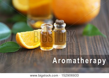 Spa composition with essence and slice of orange, closeup. Word AROMATHERAPY on background. Spa beauty concept.