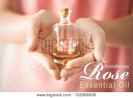 Female hand with glass bottle of essence, closeup. Text ROSE ESSENTIAL OIL on background. Spa beauty concept.