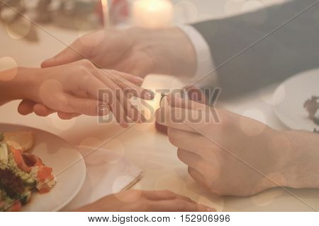 Man making marriage proposal to girlfriend at restaurant, closeup