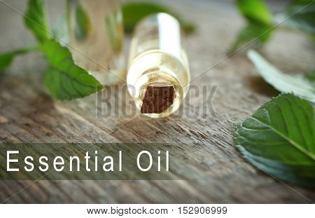 Glass bottle of essence, closeup. Text ESSENTIAL OIL on background. Spa beauty concept.