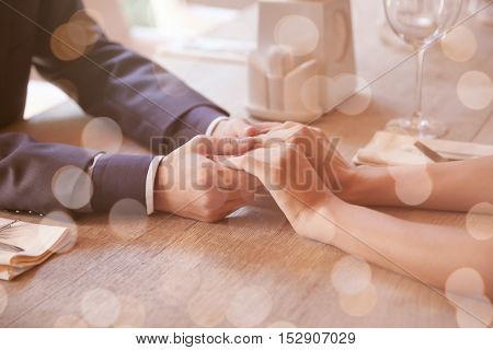 Man and woman holding hands together at restaurant, closeup