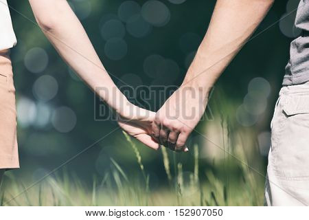 Young couple holding hands together on blurred nature background