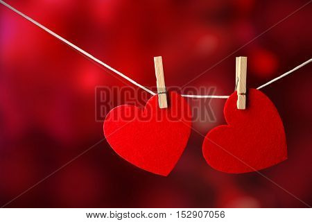 Two red hearts hanging on rope against blurred bright background.